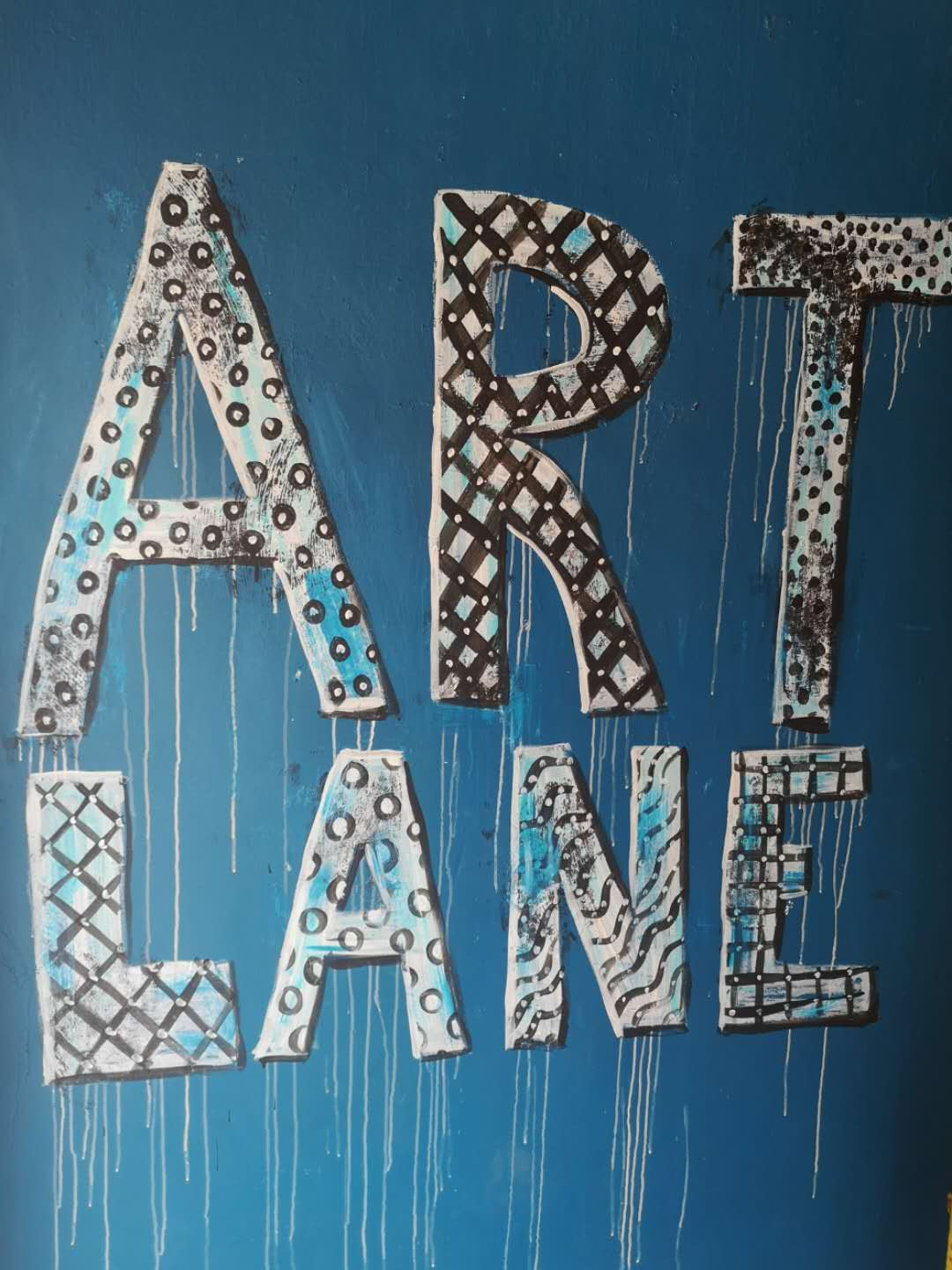 Blue background with the words Art Lane painted on it